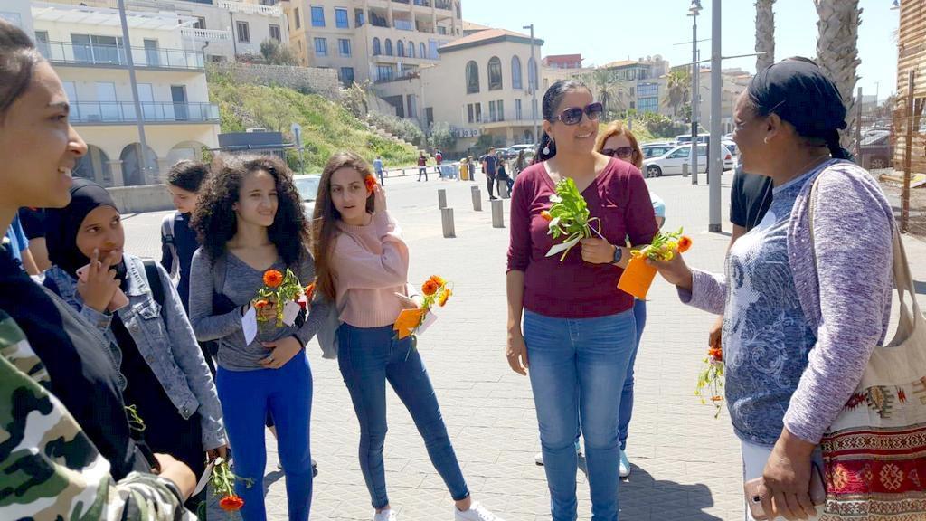 תלמידי עתיד לוד וגולדה פת מחלקים מסר עם פרח בנמל יפו